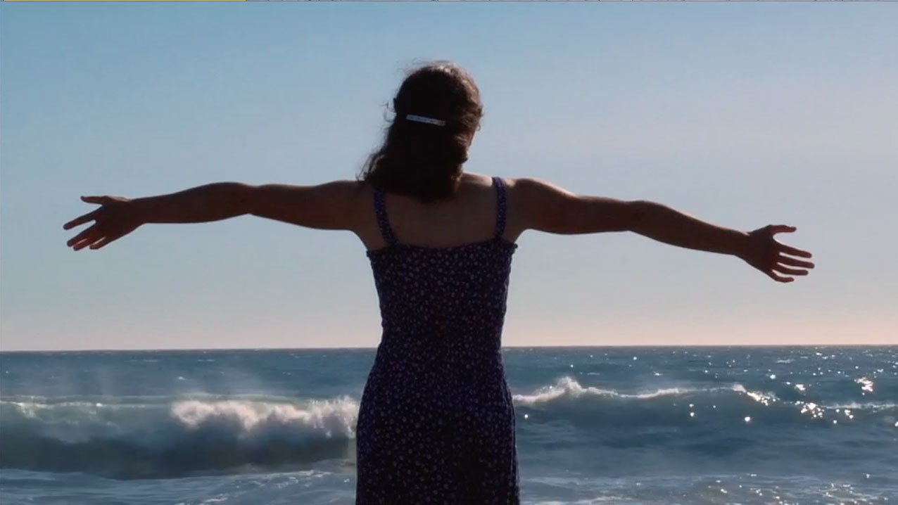 Sarah stretches out her arms in front of the ocean.
