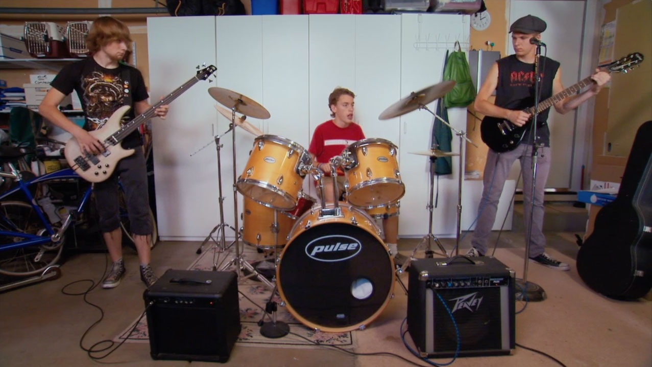 Nick plays the drums with his band mates.