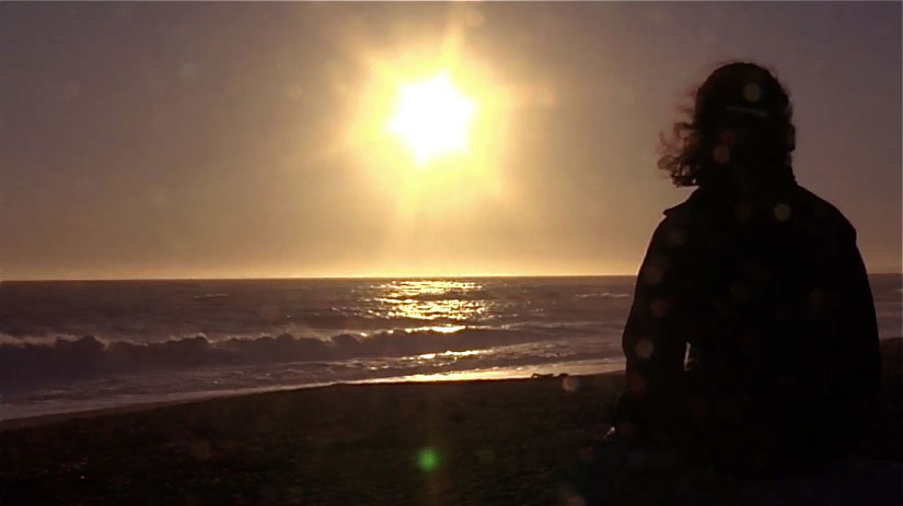 Sarah gazes out at the sunset over the ocean.