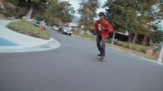 Connor skateboards down a hill.